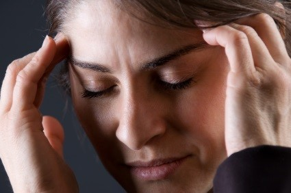 woman holding hands to head with headache