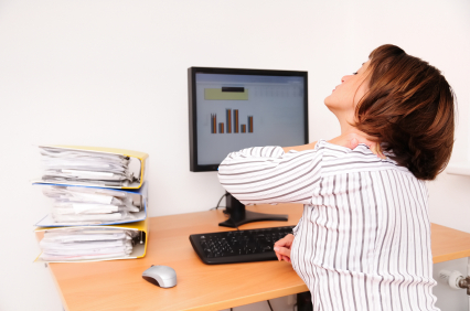 Business woman with neck pain sits on workplace with documents and monitor on table