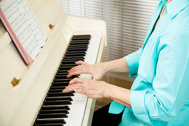 elderly lady's hands playing the piano