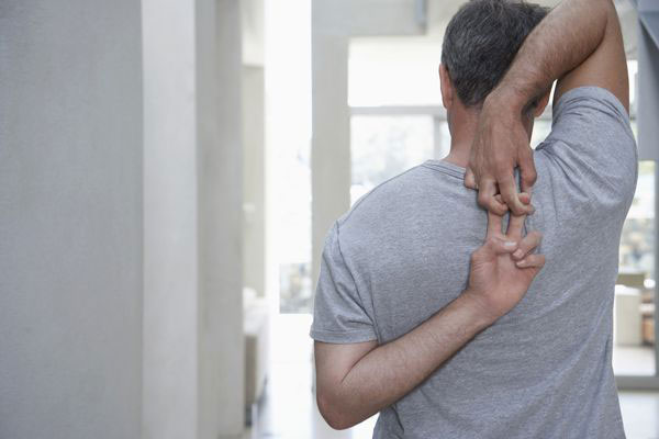 middle-aged man stretching shoulders