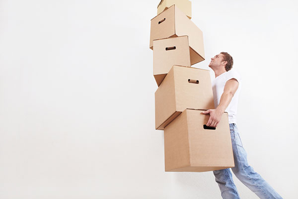 young man carries a stack of boxes